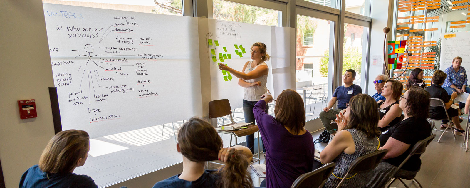 A group discusses ideas in front of a banner of sticky notes during an Innovation for Justice workshop on human trafficking survivors