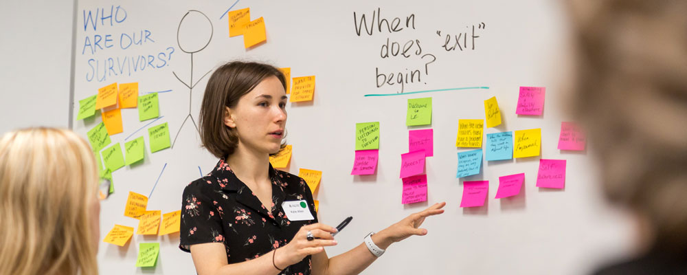 Woman speaking in front of white board with post-it notes