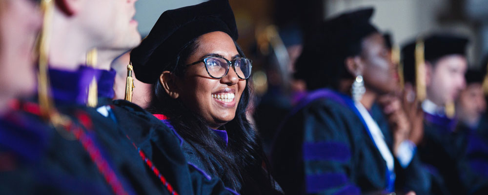 Woman in law school graduation regalia smiling