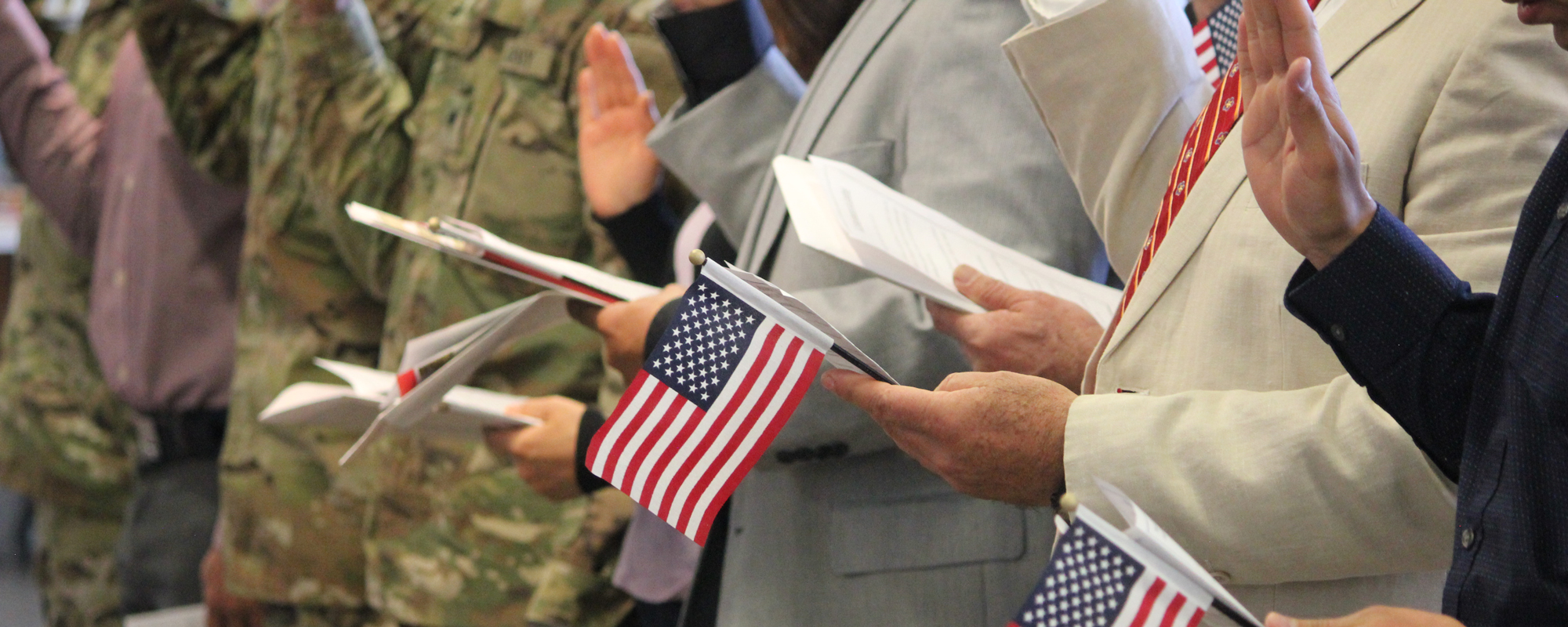 People raise their hands and hold U.S. flags at a U.S. citizen naturalization ceremony
