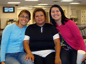 A woman smiles in between two smiling law students