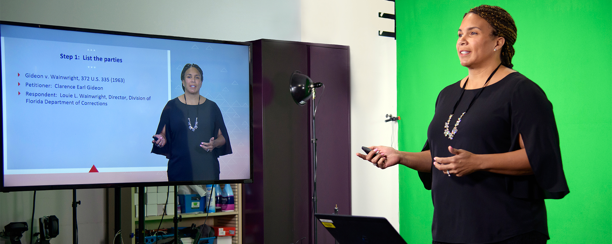 A female University of Arizona Law films a lecture in front of a green screen and monitor for an online law degree
