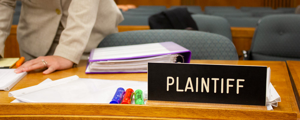 "Close-up of a desk featuring a sign that says ""Plaintiff"" along with papers, highlighters, and a woman standing behind the desk"