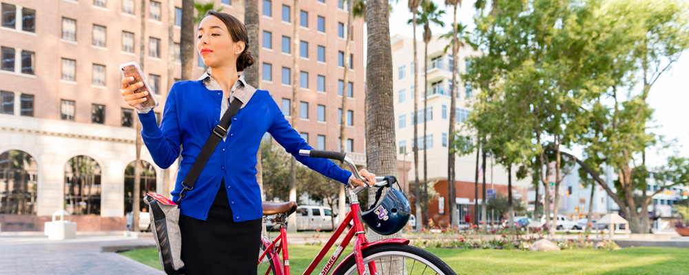 University of Arizona Law JD graduate in professional clothing looking at her phone while standing with her bike