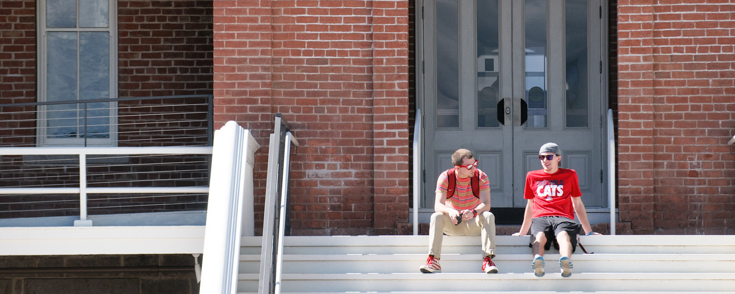 Two male students sit on the steps of the Old Main building on the University of Arizona camps