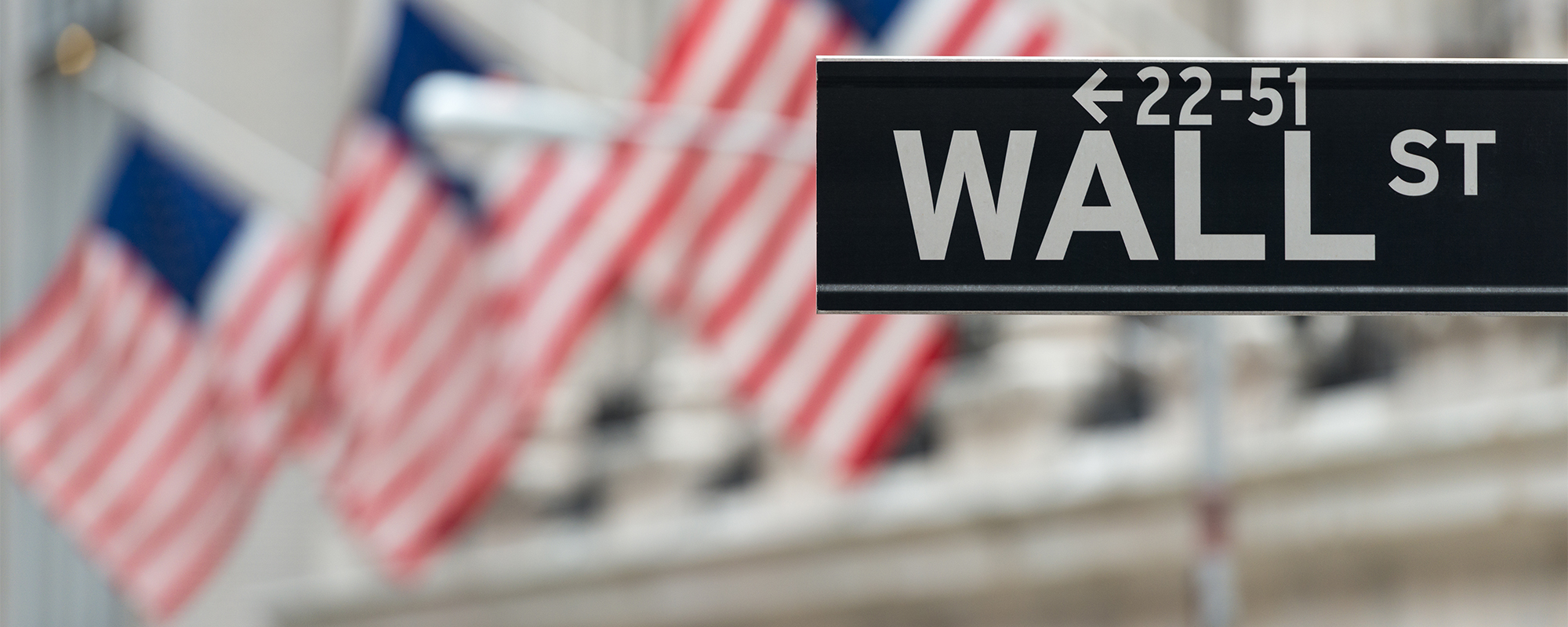 Wall Street street sign in front of American flags displayed on a building
