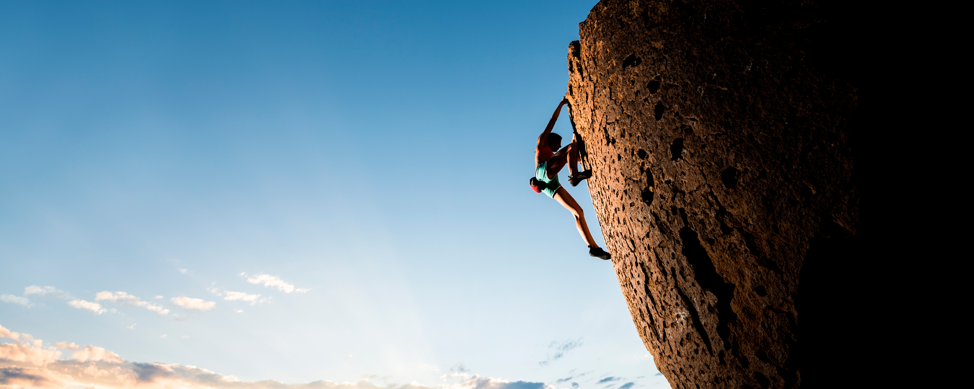 A person climbs the face of a large rock while the sun beams behind clouds in a blue sky behind them