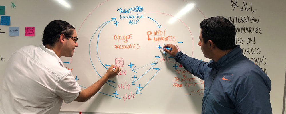 Two University of Arizona Law students work at a whiteboard on an Innovation for Justice project