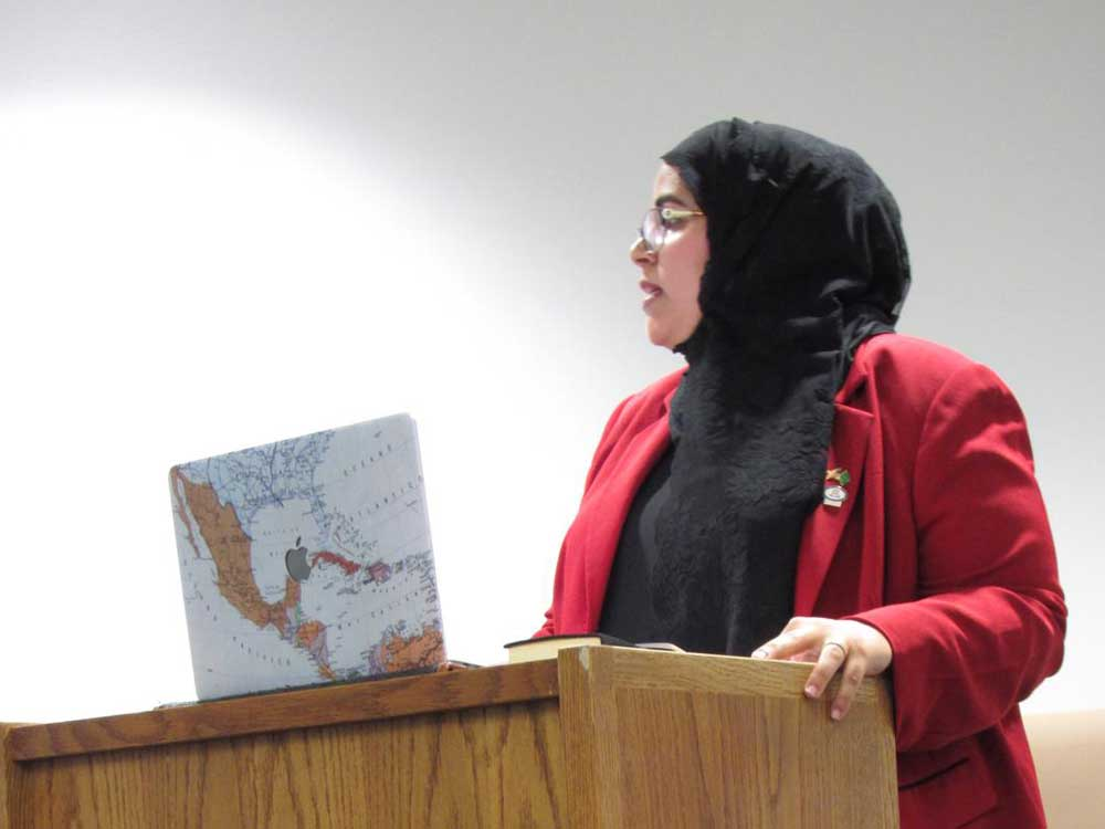 A woman stands at a podium with her laptop, giving a presentation