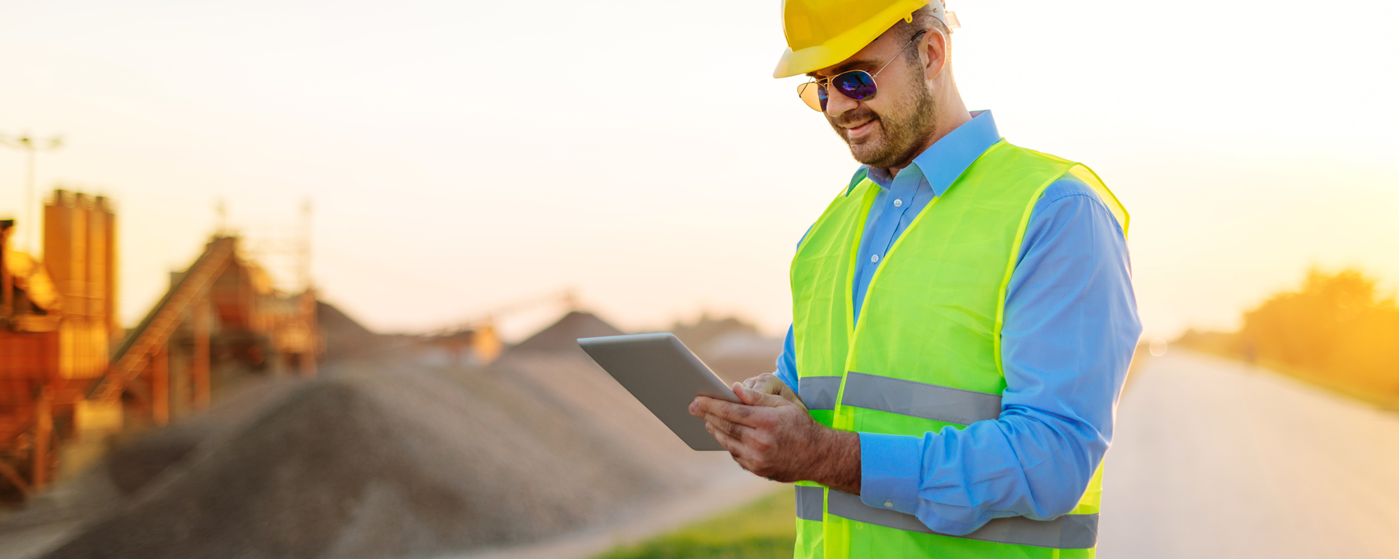 Man in vest and hardhat with tablet with a mining site in the background