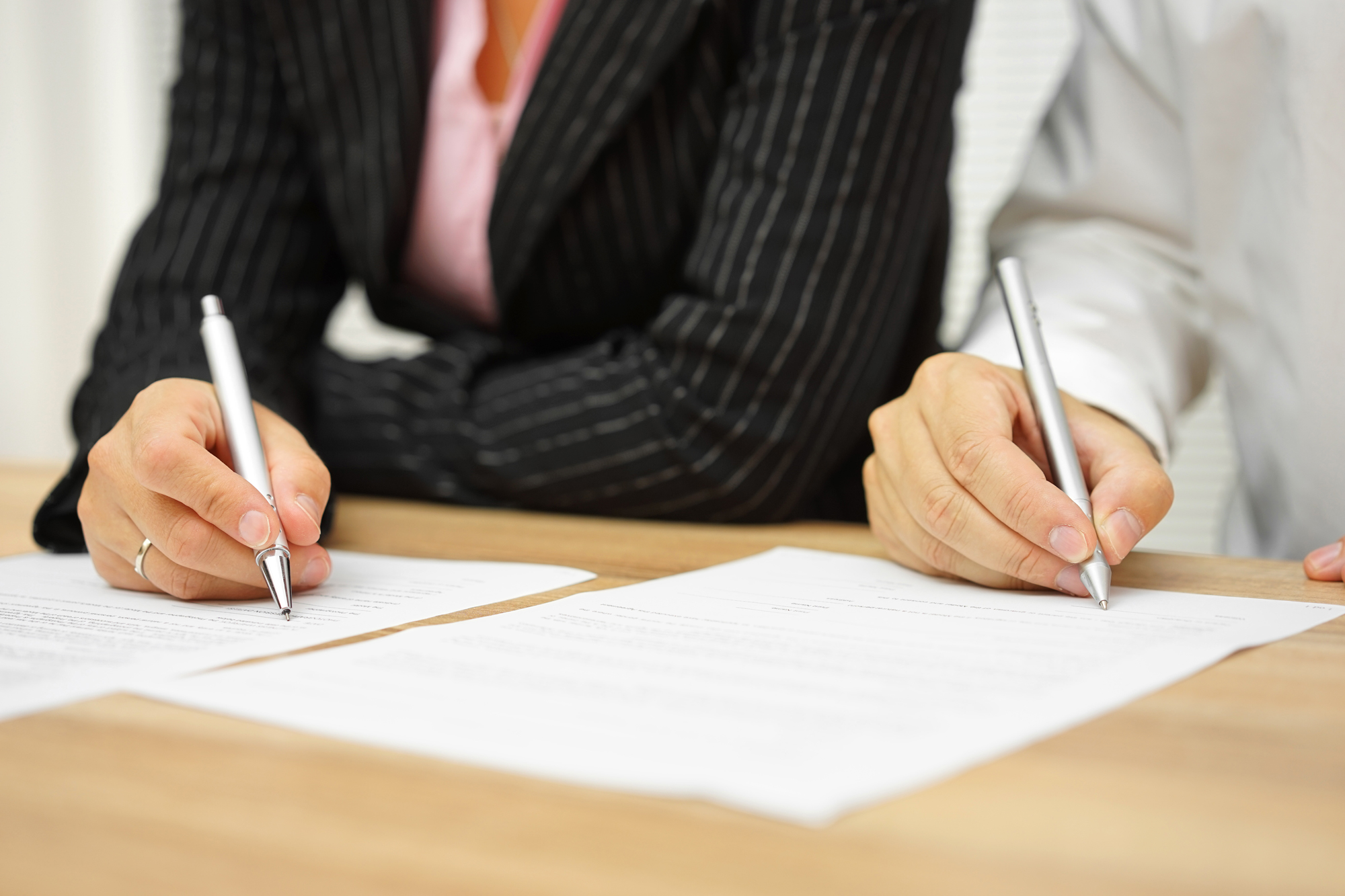 Two people in business attire sign paperwork