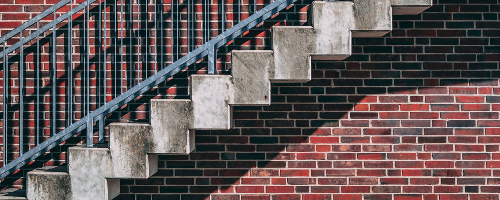 exterior stairs in front of a red brick wall