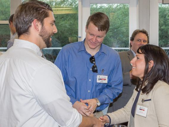 Career Development Office counselor shakes hands with student at career mixer event