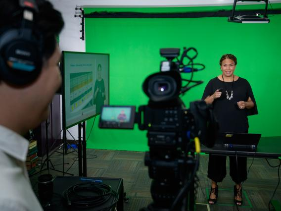A cameraman films a professor delivering a lecture in front of a green screen inside a recording studio