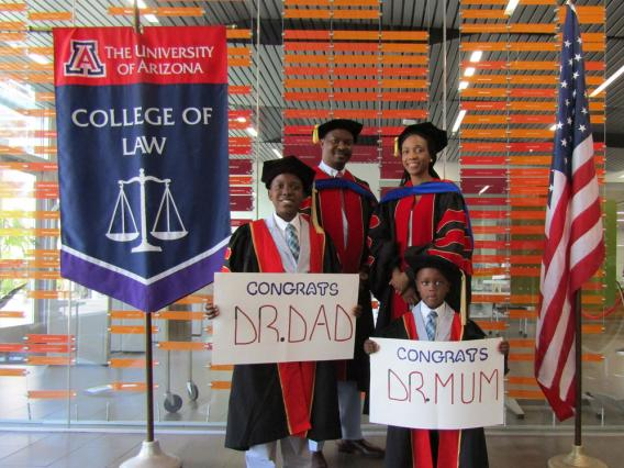 """family in graduation robes with children holding """"congrats"""" signs"""