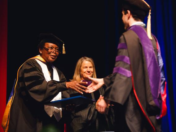 University of Arizona Law Assistant Dean of Student Affairs Willie Jordan-Curtis congratulates a student at graduation