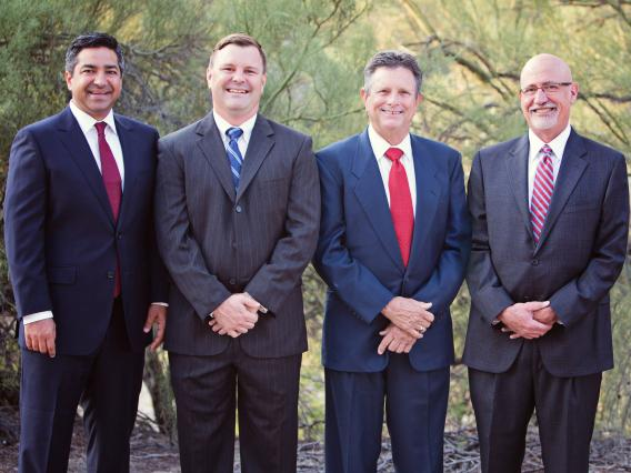 The four partners of the law firm of Schmidt, Sethi and Akmajian standing together in suits