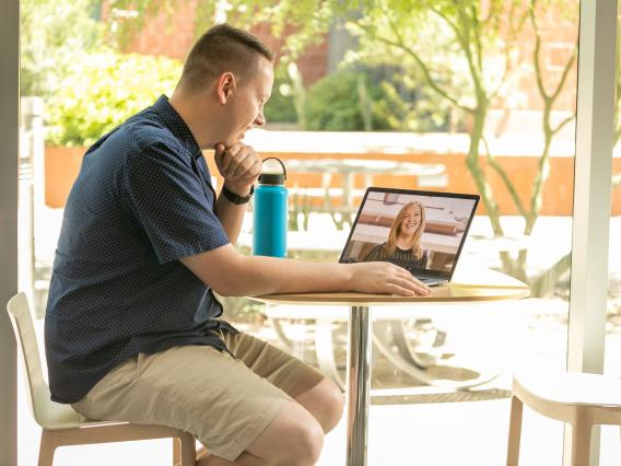 A man sits at an outdoor table working on a laptop computer