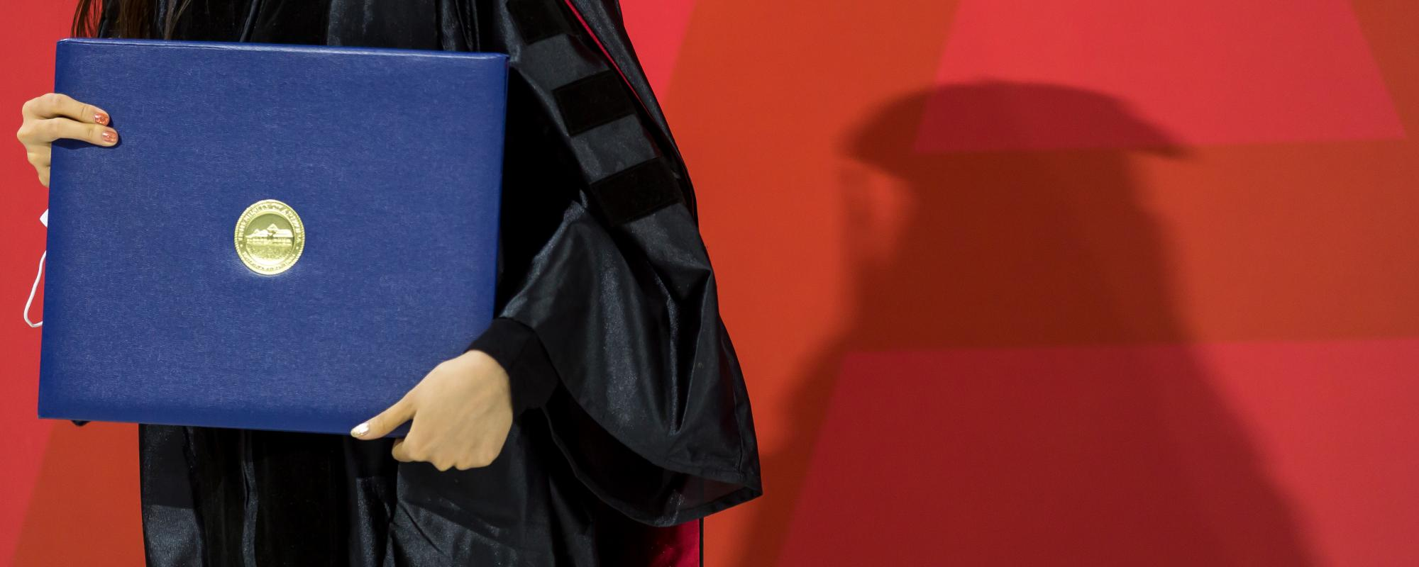 close up of person holding a diploma