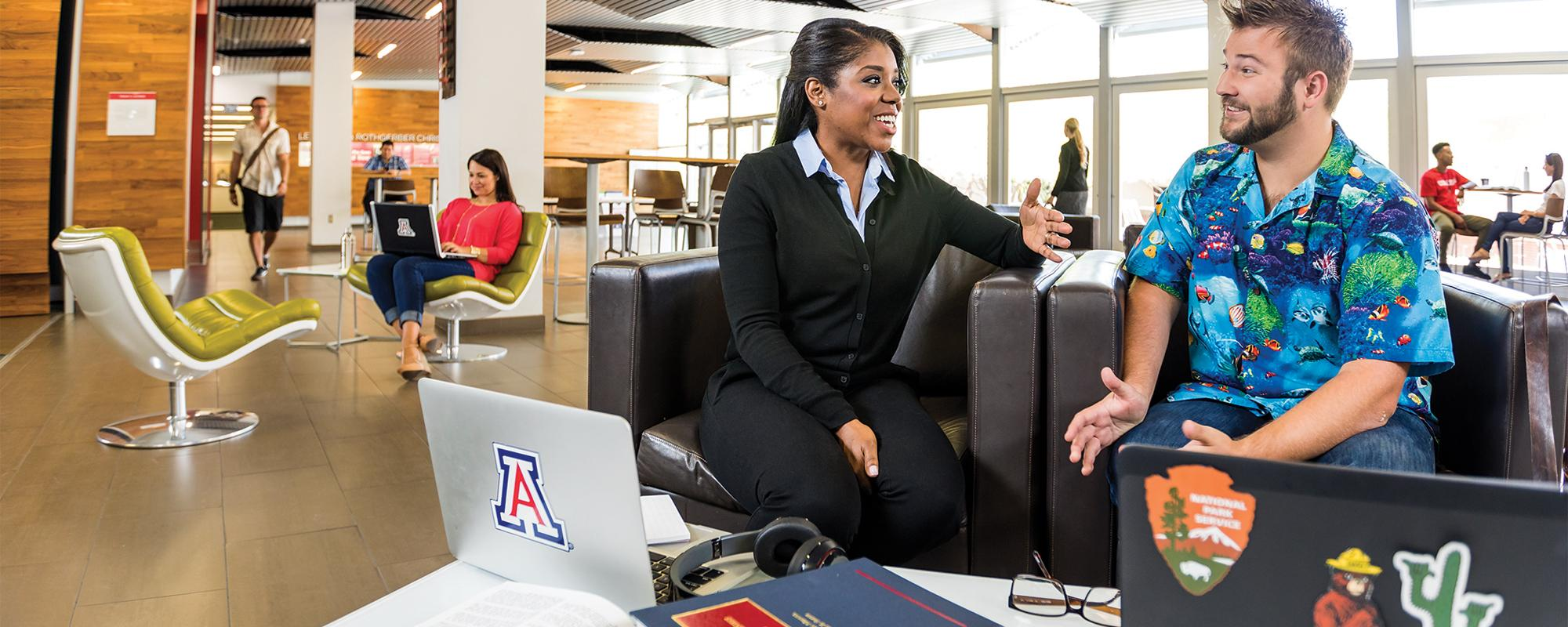 Two students sit on a couch in mid-conversation, surrounded by law textbooks, laptops and other students