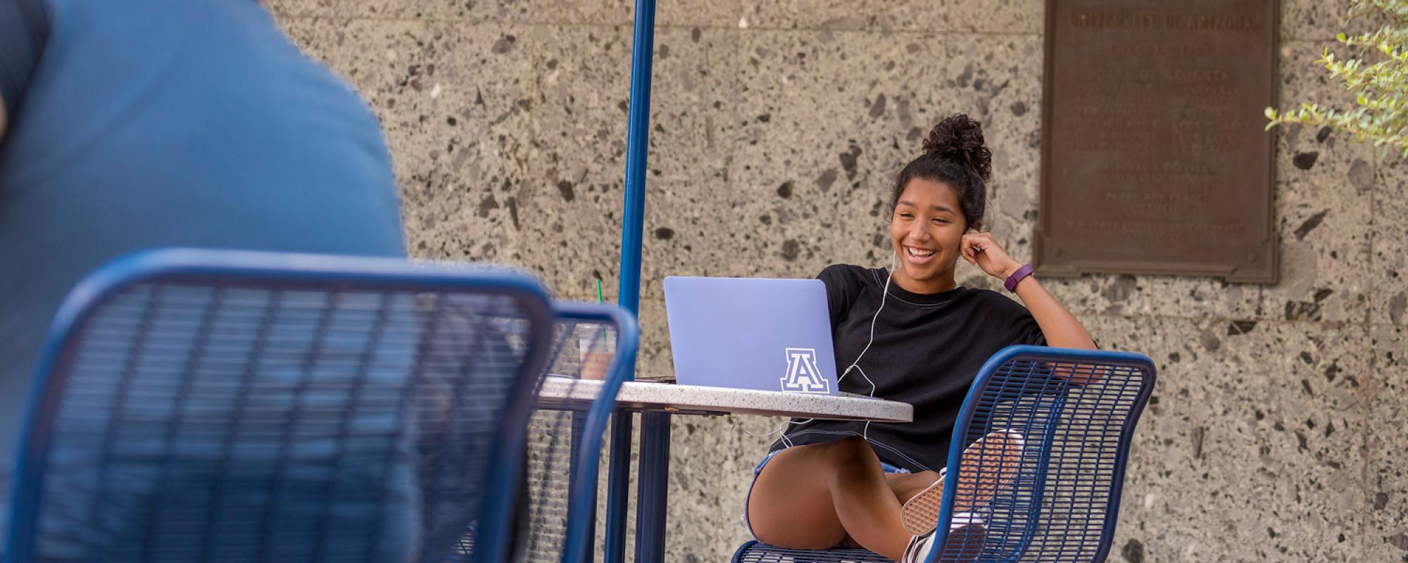 Young woman sitting outside at a table and smiling at her laptop computer