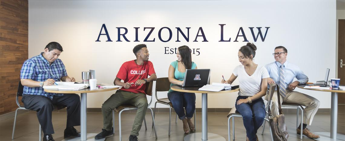 Five students study and talk while seated at tables in front of an Arizona Law sign