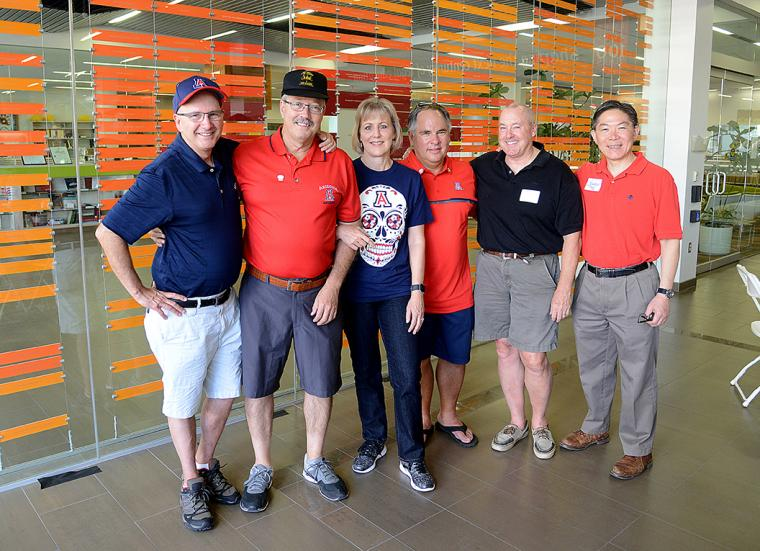 Six University of Arizona Law alumni dressed in red and blue in the lobby of the College of Law building