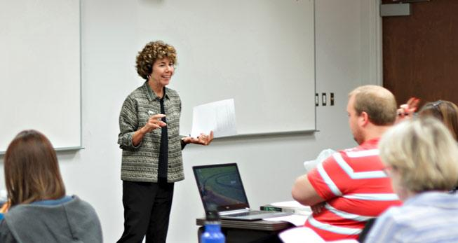 A woman, Barbara Atwood, stands at the front of a classroom, teaching a room of students.