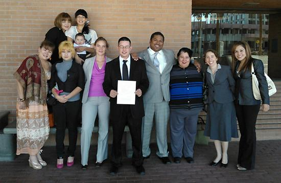 A large family with their arms around each other and a man in a suit holding a judge's order closing his deportation case