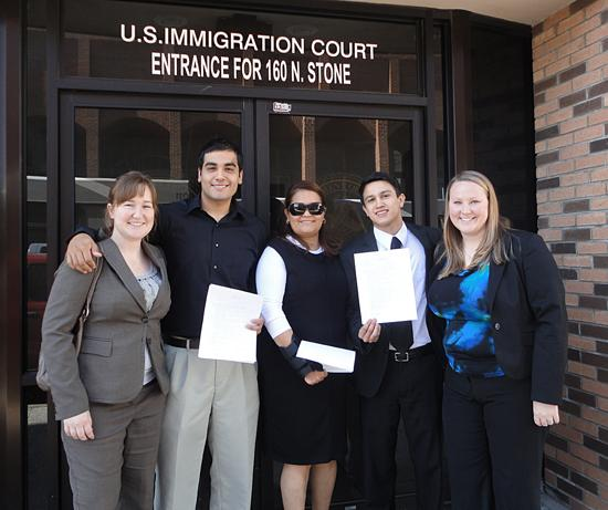 A mother, her two adult sons and two law students smile outside an Immigration Court building