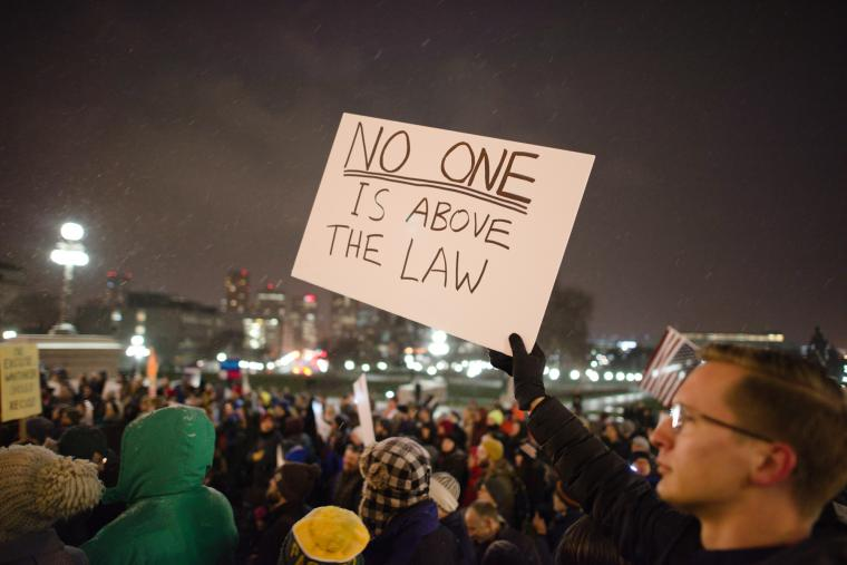 """Protester in a crowd holding a sign that reads """"No one is above the law"""" to protest President Donald Trump asking Attorney General Jeff Sessions to resign"""
