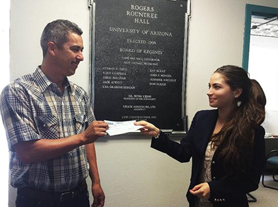 A female law student presents a male worker with a check for his unpaid wages.