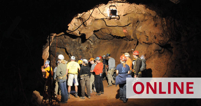 A group of people in hard hats explore a mine