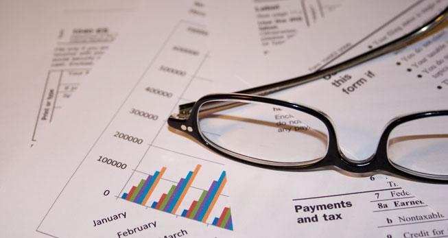 A pair of glasses rests on top of a stack of financial papers