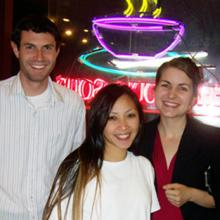 Smiling woman poses with two smiling law students in front of a neon restaurant sign