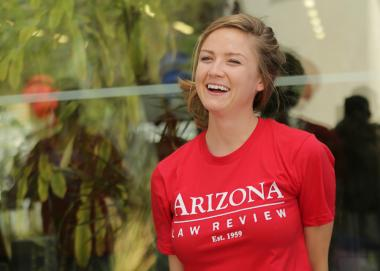 Woman in red Arizona Law Review t-shirt smiles outside the law school building