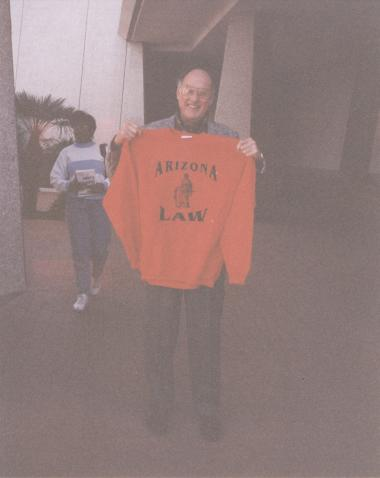 Chief Justice of the United States William Rehnquist smiles as he holds a red University of Arizona Law sweatshirt