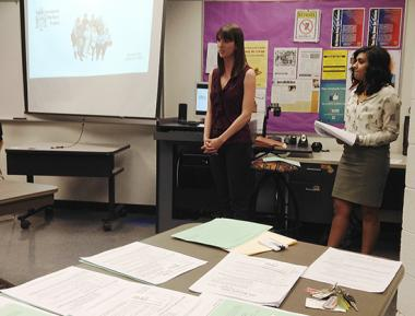 Two women stand in the front of a classroom giving a presentation