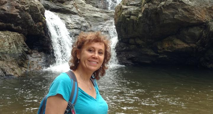 Cora Varas-Nelson stands in front of a waterfall