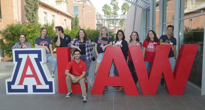 Students posing around A LAW large letters