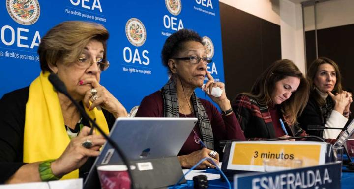 Four women listening to a speaker at an Inter-American Commission on Human Rights panel