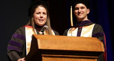 Class gift co-chairs Jillian Andrews and Storm Byrd announce the results of the Graduate 2 Service campaign at commencement. <em>Photo: David Sanders</em>.